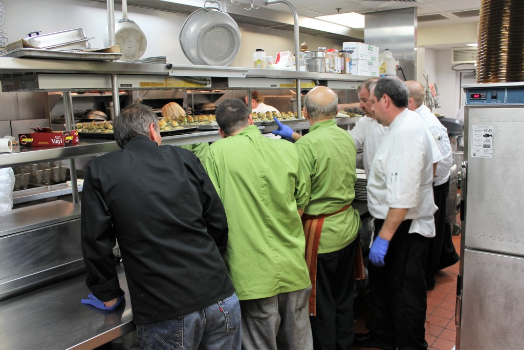 A quick meeting with the kitchen staff as they prepare to serve the 4th course